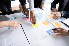 Close Up Table Full Of Papers, Diverse Businesspeople Analyzing Report In Charts And Graphs Discuss Paperwork Data Statistics At Group Meeting. Research Overview Activity, Brainstorm Teamwork Concept