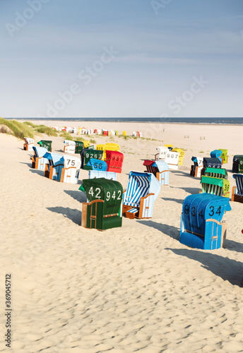 Valokuvatapetti Colorful beach chairs in white sand in the morning on the Frisian island of Juist
