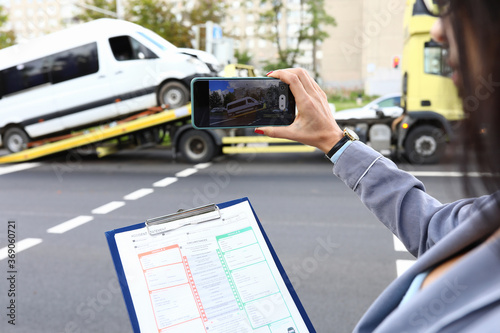 An insurance agent takes photo of crashed car after an accident on smartphone Canvas Print