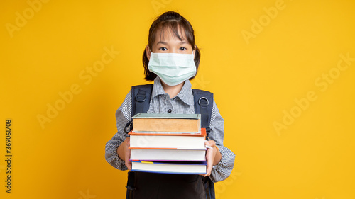 Obraz Thai young girl wearing face mask, Asian kid holding lots of books isolated on yellow or orange background, learning and back to school during coronavirus or covid 19 - fototapety do salonu
