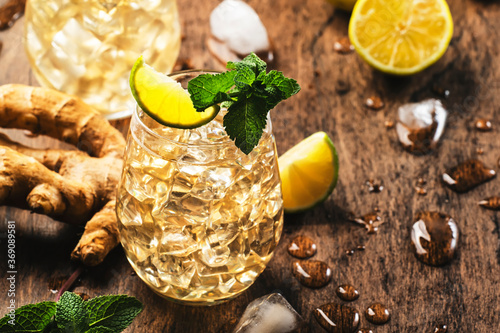 Obraz Golden Ginger Ale Beer Cocktail with Lime, Lemon and Mint in glaass on wooden table, copy space - fototapety do salonu