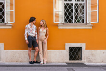 Young Couple Looking Each Other Standing On The Sidewalk.