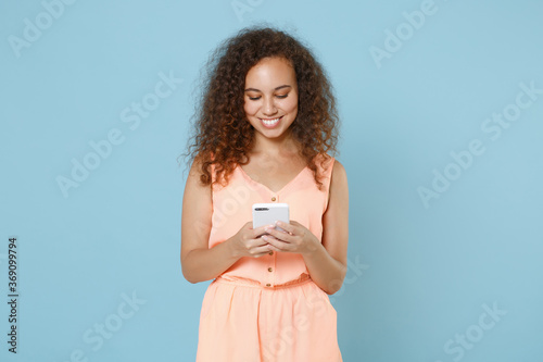 Smiling young african american girl in pastel summer clothes isolated on blue wall background studio portrait. People lifestyle concept. Mock up copy space. Using mobile cell phone typing sms message.
