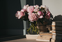 Pink Peonies And Stacks Of Books