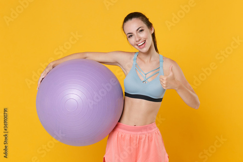 Obraz Cheerful young fitness sporty woman girl in sportswear working out isolated on yellow background studio portrait. Workout sport motivation concept. Mock up copy space. Hold fitball, showing thumb up. - fototapety do salonu