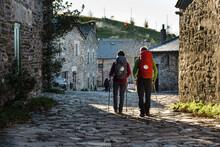 Couple Of Pilgrims Walking Along Rural Village In Their Way To Santiago De Compostela