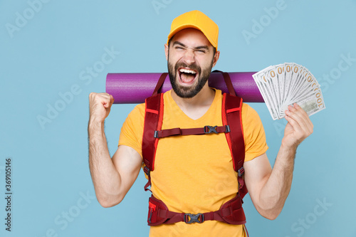 Obraz Happy traveler man with backpack isolated on blue background. Tourist traveling on weekend getaway. Tourism discovering hiking concept. Hold fan of cash money in dollar banknotes doing winner gesture. - fototapety do salonu