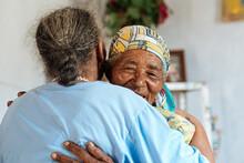 Senior Females Hugging Indoors