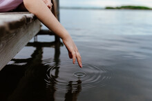 A Girl Dips Her Hand Into Lake...