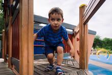 Little Boy Going Bending Down On Playground Platform