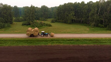 Tractor Loaded With Haystacks Rides On Road