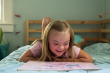 Little Girl With Down Syndrome Reading Book