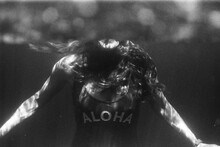 Underwater Potrait Of Woman In Swimsuit Saying Aloha