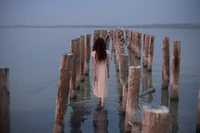 The Girl In The Dress Goes Between The Wooden Pillars In The Water