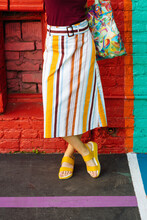 Woman In Striped Skirt And Yellow Flip Flops