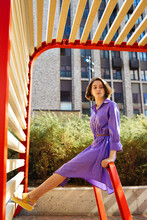 Girl In A Purple Dress Sits On A Red Metal Construction