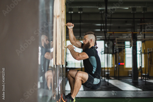 Strong and healthy man climbing inside a crossfit gym.