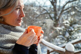 Mature woman drinking hot beverage in the winter time