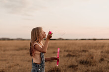 Portrait Of A Girl Playing With Bubbles At Sunset.