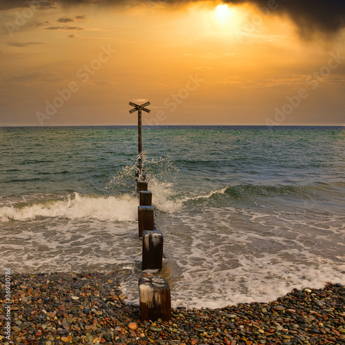 Photo Wooden pillars and metal cross on Findhorn Beach, Moray Coast, Scotland with dramatic sunrise