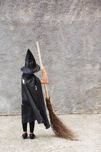 Girl In Halloween Costume Having Fun. A Little Girl In A Witch Costume Is Playing Outdoor. Little Girl Witch Costume With A Broom