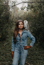 A Woman In Her Twenties Posing For A Portrait With An Owl In A Forest