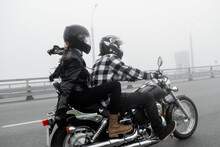 Attractive Couple Riding Vintage Motorcycle Across The Bridge Over River, Foggy Weather.