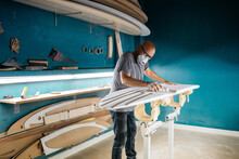 Surf Shaper Making A Board With A Sandpaper