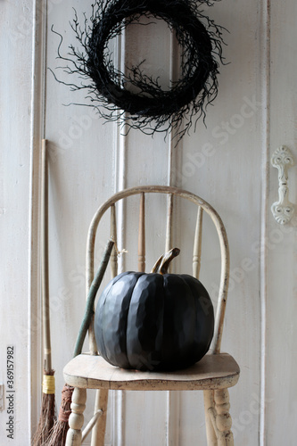 Black pumpkin on old chair with wreath