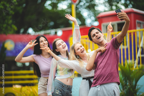 Obraz Group of happy best friends laughing and having fun at amusement park, holiday travel with friends concept - fototapety do salonu