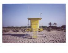 Yellow Wooden Tower Of Lifeguard On Coast Line Among Sand.