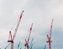 Colorful Tower Cranes Reaching Into The Sky