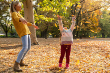Mom And Daughter Spending Sunny Autumn Day In The Park