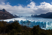 Ice Cliff Wall Behind Trees And Vegetation In A Valley Surrounded By Snowy Mountains At Perito Moreno Glacier In Argentina.