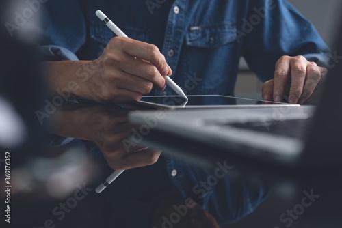 Fototapeta Male graphic designer using stylus pen working on digital tablet on office