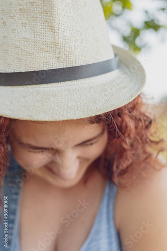 red-haired curly-haired girl in a summer braided headgear and jeans dress posing in the village Canvas Print