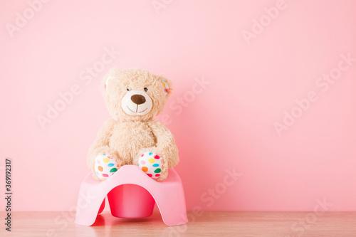Brown teddy bear sitting on baby potty on floor Wallpaper Mural