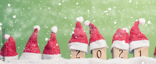 Obraz Many hats of Santa in a row with snow, New Year 2021 on wooden blocks, Christmas background, panoramic view - fototapety do salonu