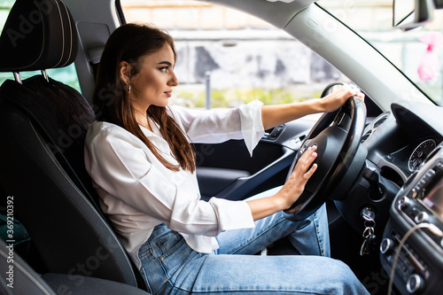 Photo Young pretty woman hand pressing the horn button while driving a car through the road