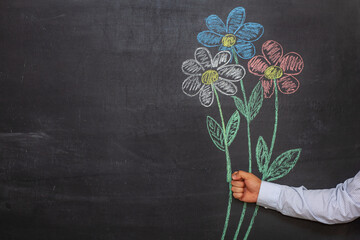 A man's hand holds flowers drawn in chalk on a chalkboard