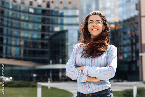Fotografie, Obraz Portrait of confident smiling young businesswoman with glasses standing in city