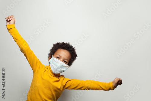 Obraz Portrait of funny black child boy in medical protective face mask having fun - fototapety do salonu