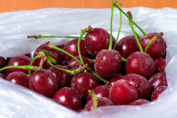 frozen cherries are covered with ice crystals and frost for winter home preparation in the freezer.