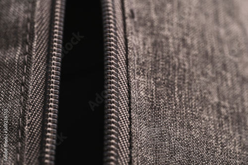 Closeup vertical open zippers of gray cloth bag in low light mood Canvas Print