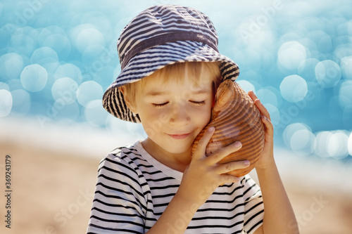 Fotografering little boy smiling at the beach in hat andholding shell