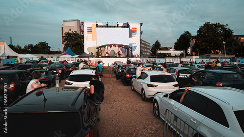 Valokuva Live show concert in a parking with a lot of cars parked in front of a big scenery to hear music and watch the spectacle inside the car
