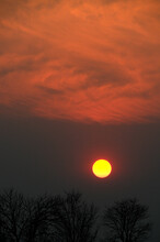Fiery Clouds Burning While The African Sun Is Sliding Down Into The Hanging Dust