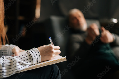 Fotografiet Close-up of woman psychologist taking notes in notebook, mature man patient answering questions in office passing psychological test