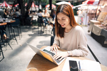 Young Adult Asian Woman Work With Laptop Computer At Outdoor Cafe