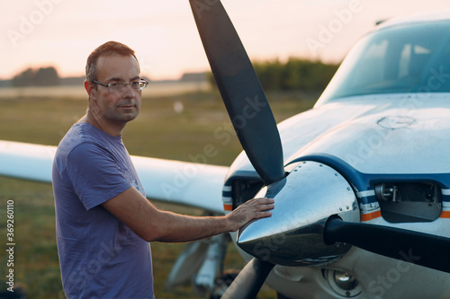 Photo Pilot man standing next to a small private airplane